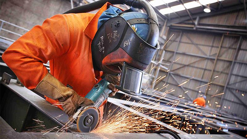 Man wearing welding mask and cutting metal
